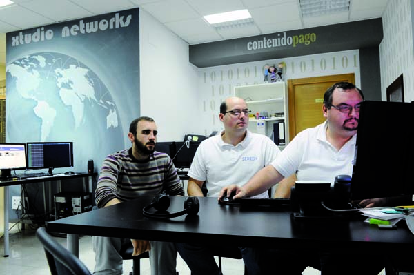 Víctor Alves Dobao with brothers Daniel and Julio Brasa Blanco at the Xtudio Networks headquarters in A Rúa. Below, a picture of the three checking a website